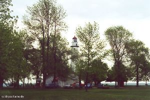 Distance shot of the lighthouse through some trees.