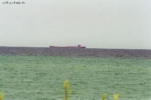 A freighter passes by Point Betsie Lighthouse.