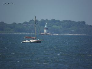 A sailboat passes by the Latimer Reef Lighthouse.