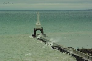 Waves crash over the pier.