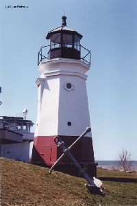 Lighthouse with anchor in front of it.