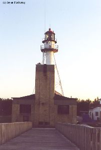 The lighthouse towers over an outbuilding.